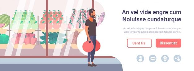 Uomo in possesso di borse per la spesa a piedi davanti a frutta fresca verdura moderna supermercato negozio vetrina ragazzo cliente piena lunghezza personaggio dei cartoni animati piatta copia spazio