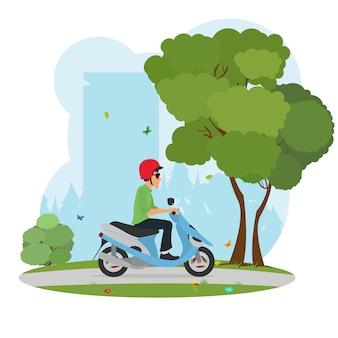 Uomo in un casco in sella a uno scooter intorno al parco cittadino.
