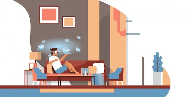 Uomo indossare occhiali digitali tocco realtà virtuale uccelli volanti vr visione auricolare concetto innovazione salone interno piano orizzontale