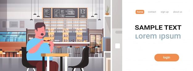 Uomo mangia hamburger oltre dimensioni ragazzo seduto al tavolo del ristorante malsano cibo concetto moderno ristorante