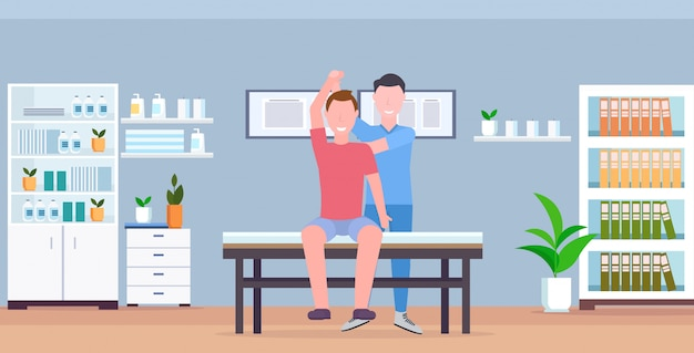 Uomo paziente seduto sul tavolo massaggiatore terapeuta facendo trattamento curativo massaggiando paziente paziente sport manuale concetto di terapia fisica moderna clinica ospedale stanza orizzontale interno