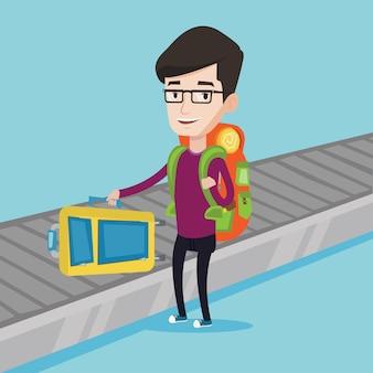 Uomo raccogliendo valigia sul nastro trasportatore bagagli
