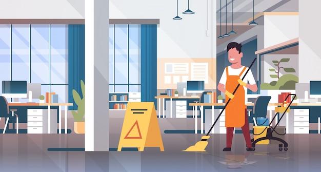 Uomo rastrellamento piano bidello detergente maschio in uniforme servizio di pulizia carrello carrello con forniture interne creativo ufficio centro di co-working