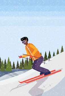 Uomo sciatore che scivola giù per la collina