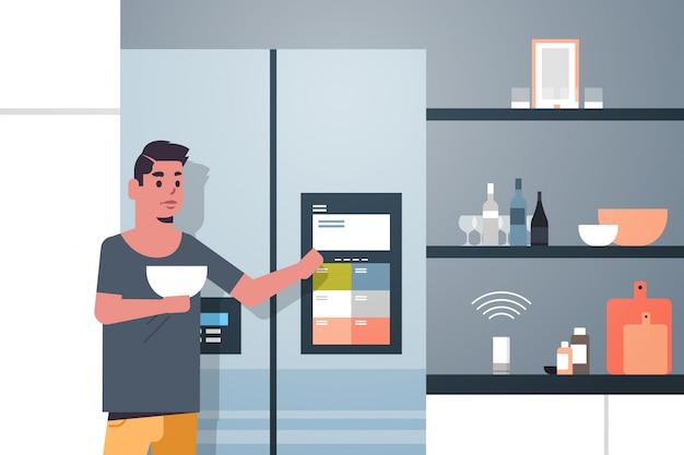 Uomo toccando lo schermo del frigorifero con altoparlante intelligente