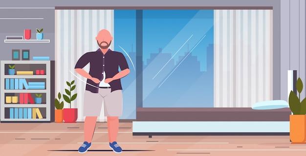 Uomo triste abbottonatura camicia sovrappeso casual ragazzo in piedi posa stile di vita malsano obesità concetto moderno casa appartamento camera da letto interno appartamento a figura intera orizzontale