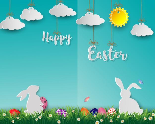 Uova di pasqua con i conigli bianchi su erba verde