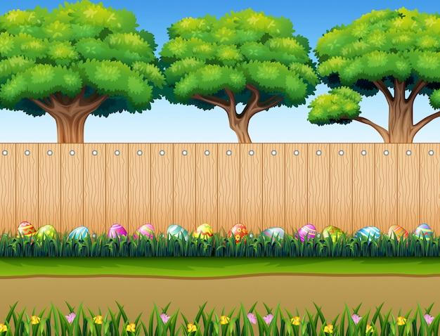 Uova di pasqua decorative sull'erba con il recinto di legno