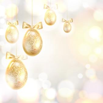 Uova di pasqua dorate sopra bokeh sfocato e sfondo grigio.