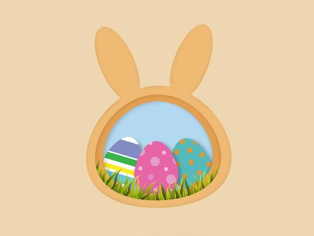 Uova di pasqua ed erba nel telaio a forma di coniglietto