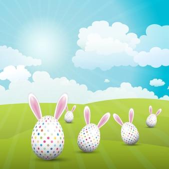 Uova di pasqua sveglie con le orecchie del coniglietto in un paesaggio soleggiato