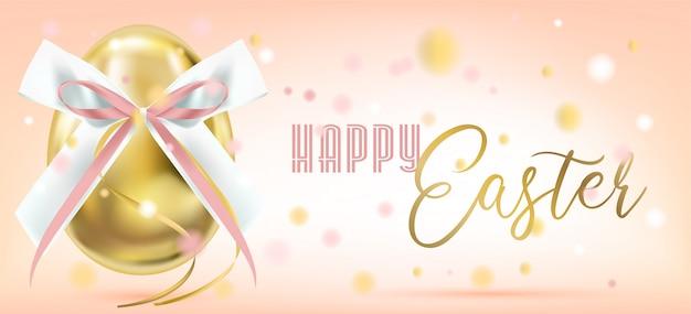 Uovo di pasqua dorato con fiocco di seta rosa e coriandoli