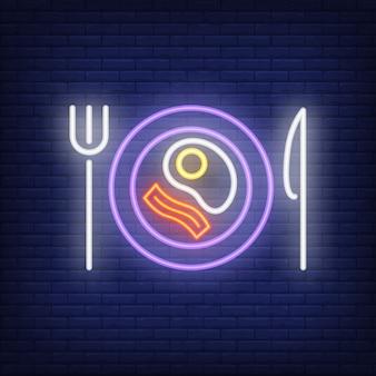 Uovo fritto e pancetta sul piatto con coltello e forchetta insegna al neon