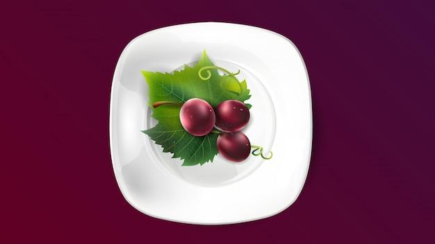 Uva rossa su una foglia dell'uva in un piatto bianco.