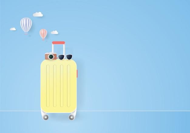 Valigia gialla con occhiali da sole e macchina fotografica per il viaggio sul blu pastello