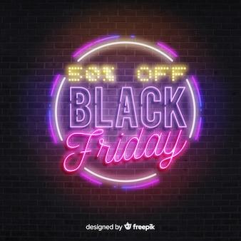 Venerdì nero rotondo alle luci al neon sul muro di mattoni