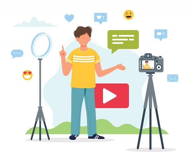 Video blogger che registra video con videocamera e luce.