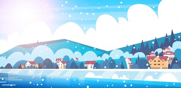 Vista congelata del fiume con le piccole case di campagna sulle montagne hills concetto del paesaggio di inverno