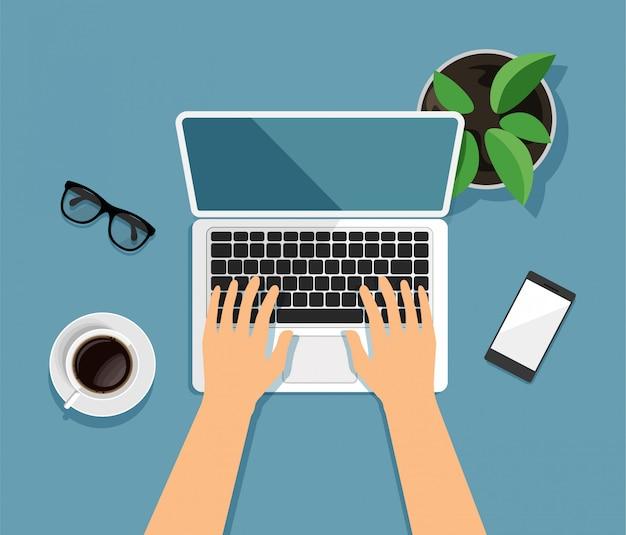 Vista dall'alto dell'area di lavoro. scrivania moderna da lavoro in stile trendy. le mani stanno scrivendo su un computer. computer portatile, vetri, smartphone, caffè, vaso da fiori isolato su fondo blu.