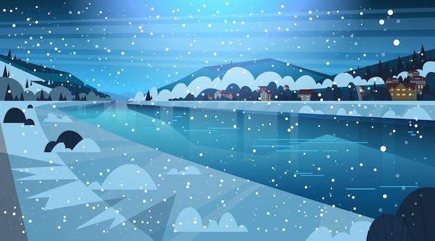 Vista di notte del fiume congelato con le piccole case di campagna sul concetto del paesaggio di inverno delle colline delle montagne