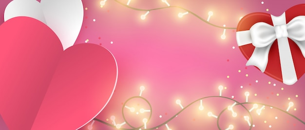 Vista superiore del fondo dell'insegna di san valentino. taglio della carta di forma del cuore e contenitore di regalo e luce d'ardore sulla tavola di legno.