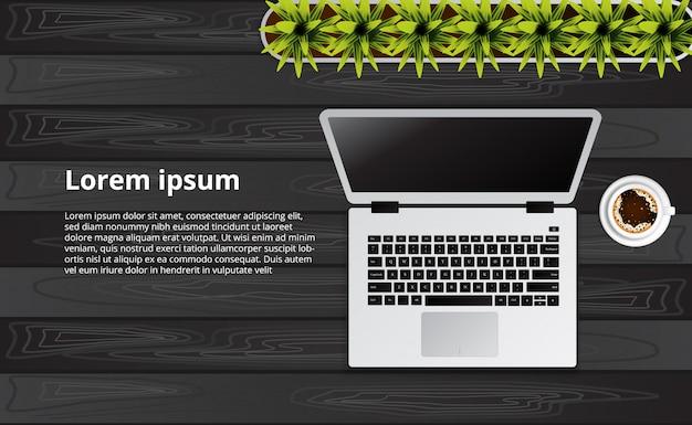Vista superiore semplice portatile pulito sulla scrivania in legno con pianta
