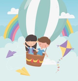 Volo del ragazzo e della ragazza del giorno dei bambini felici con la mongolfiera