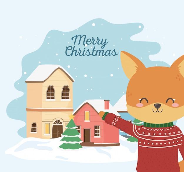 Volpe sveglia di celebrazione di buon natale con l'albero brutto della neve della città del maglione