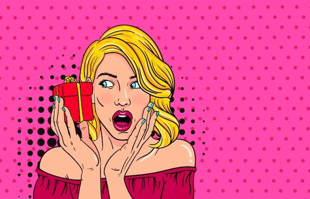 Wow faccia pop art della ragazza sorpresa di moda bocca aperta con valentine present in mano.
