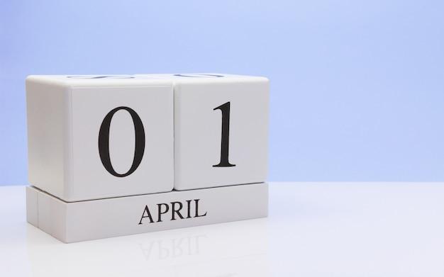 01 april. dag 01 van de maand, dagelijkse kalender op witte tafel met reflectie