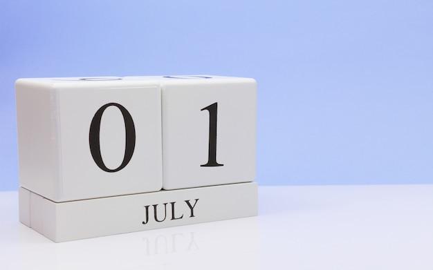 01 juli. dag 1 van de maand, dagelijkse kalender op witte tafel met reflectie, met lichtblauwe achtergrond.
