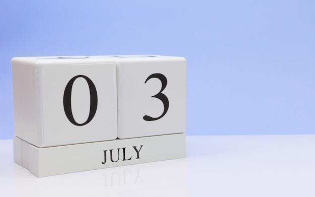 03 juli. dag 3 van de maand, dagelijkse kalender op witte tafel met reflectie, met lichtblauwe achtergrond.