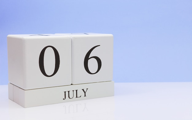 06 juli. dag 6 van de maand, dagelijkse kalender op witte tafel met reflectie, met lichtblauwe achtergrond.
