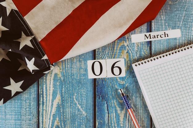 06 maart kalenderdag vlag van de verenigde staten van amerika symbool van vrijheid en democratie met lege kladblok en pen op kantoor houten tafel