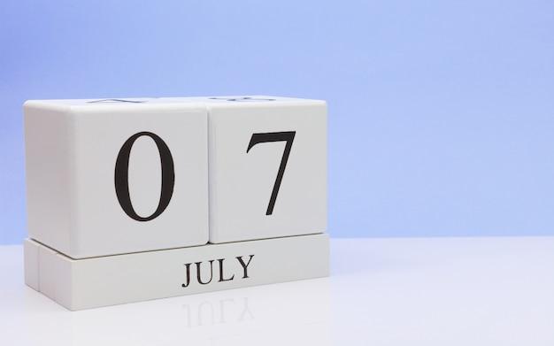 07 juli. dag 7 van de maand, dagelijkse kalender op witte tafel met reflectie, met lichtblauwe achtergrond.