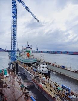 07312021 nederland delfdzijl een schip slepen met een sleepboot voor reparatie naar een droogdok op een scheepswerf