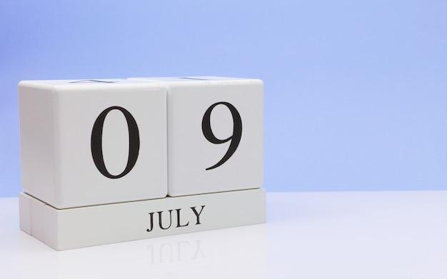 09 juli. dag 9 van de maand, dagelijkse kalender op witte tafel met reflectie, met lichtblauwe achtergrond.