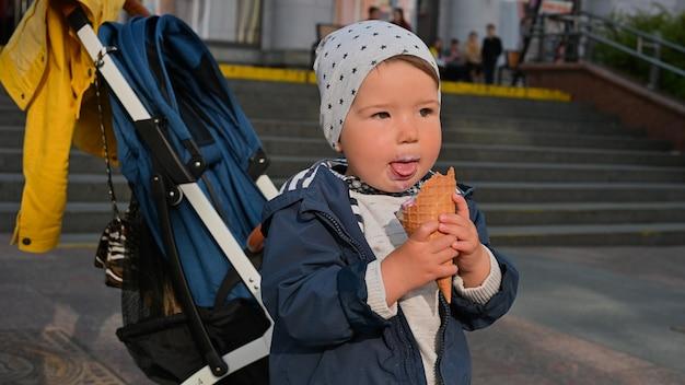 1-2 jaar oud kind eet ijs op straat. wandelwagen achtergrond