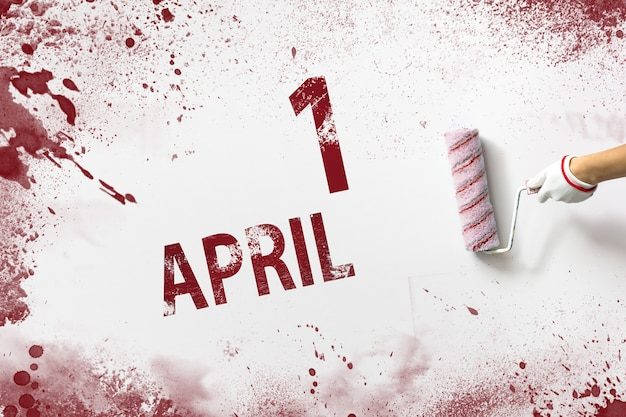 1 april . dag 1 van de maand, kalenderdatum. de hand houdt een roller met rode verf vast en schrijft een kalenderdatum op een witte achtergrond. lente maand, dag van het jaar concept.