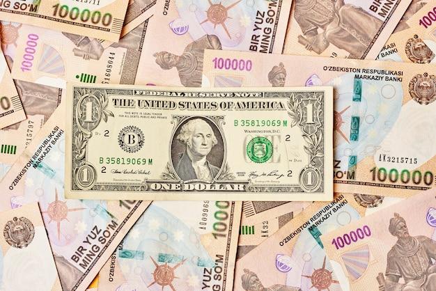 1 dollar us dollar biljet en stapel oezbeekse bedragen wisselkoers financieringsconcepten