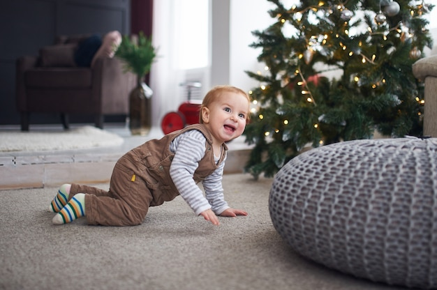 1 éénjarige babyjongen die op vloer thuis kruipt.