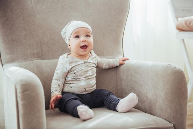 1 jaar meisje draagt stijlvolle kleding, zittend in een vintage stoel in de kamer.