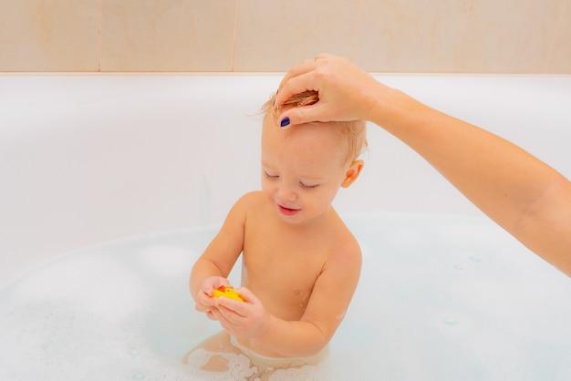 1-jarige baby baadt in een douche. kleine nieuwsgierige mooie babyzitting in witte badkamers met nat schuimhaar dat weg kijkt. gezonde kinderen