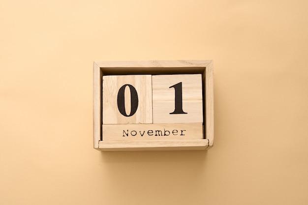 1 november. dag 1 van november ingesteld op houten kalender op beige