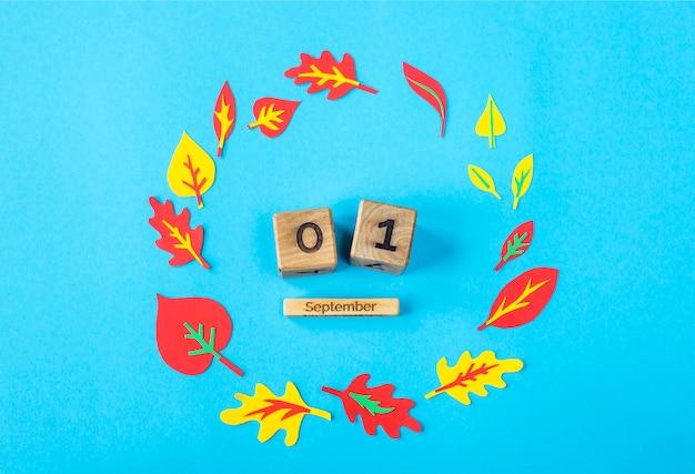 1 september op een houten kalender op een blauwe achtergrond onder de papieren herfstbladeren