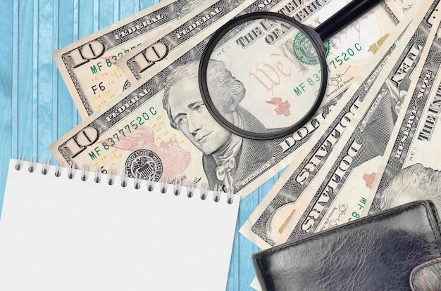 10 dollarbiljetten en vergrootglas met zwarte tas en blocnote
