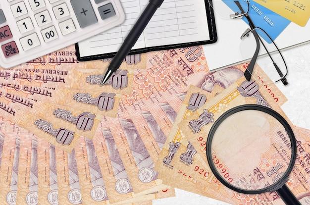 10 indiase roepiesrekeningen en rekenmachine met bril en pen. belastingbetalingsseizoenconcept of investeringsoplossingen. op zoek naar een baan met een hoog salaris