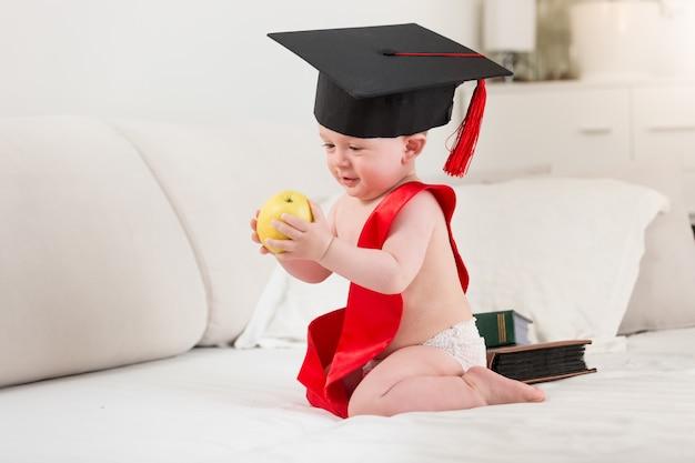 10 maanden oude babyjongen in afstudeerpet en lint met gele appel