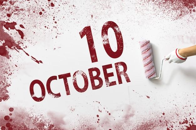 10 oktober. dag 10 van de maand, kalenderdatum. de hand houdt een roller met rode verf vast en schrijft een kalenderdatum op een witte achtergrond. herfstmaand, dag van het jaarconcept.