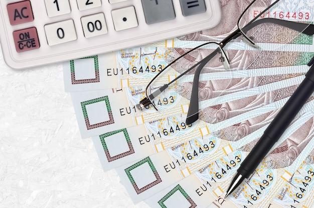10 poolse zloty facturen ventilator en rekenmachine met bril en pen.